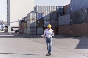 Businessman wearing safety helmet using mobile phone at industrial site - UUF20407