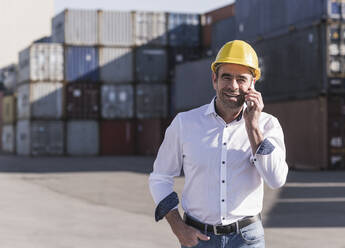 Portrait of smiling businessman on the phone in front of cargo containers - UUF20410