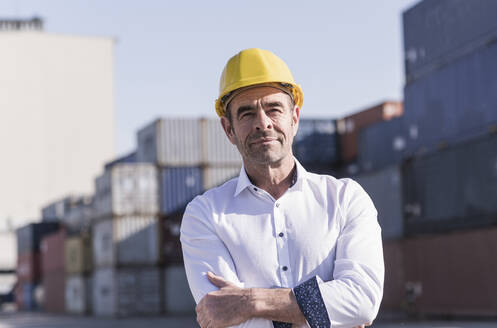 Portrait of businessman wearing safety helmet in front of cargo containers - UUF20413