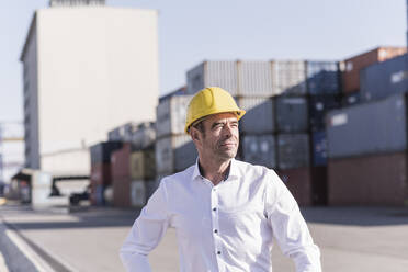 Portrait of businessman wearing safety helmet at industrial site - UUF20416