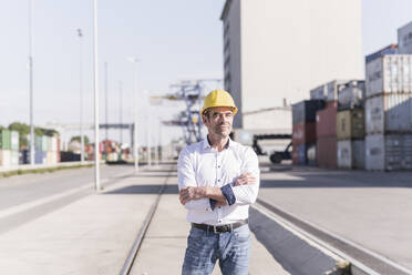 Portrait of businessman wearing safety helmet at industrial site - UUF20419