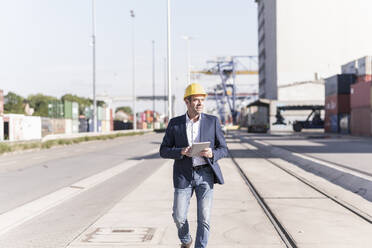 Businessman with digital tablet at industrial site - UUF20425