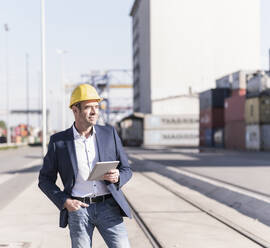 Businessman wearing safety helmet with digital tablet at industrial site - UUF20428
