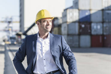 Portrait of businessman wearing safety helmet at industrial site - UUF20434