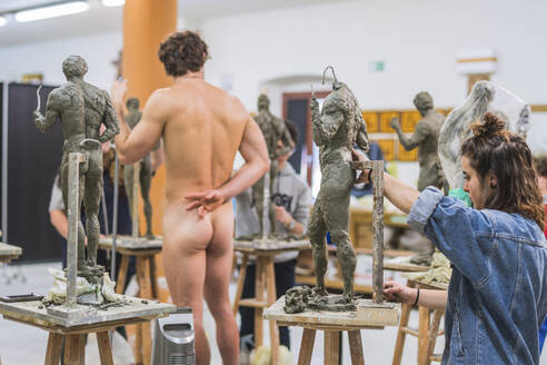 Female student forming sculpture, nude model in the background - FBAF01559