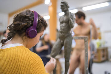 Female student with headphones working on sculpture, nude model in the background - FBAF01562