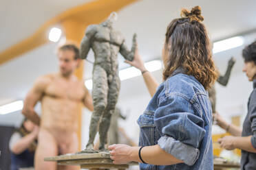 Female student forming sculpture, nude model in the background - FBAF01565