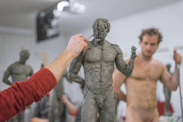 Student forming sculpture, nude model in the background - FBAF01571