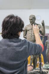 Female student forming nude sculpture - FBAF01577