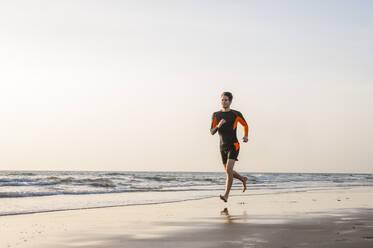 Man running at the sea, Gran Canaria, Spain - DIGF12571