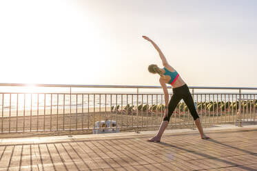 Sporty woman stretching at the seafront at sunrise, Gran Canaria, Spain - DIGF12574
