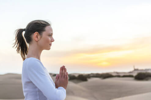 Woman meditating at sunset in the dunes, Gran Canaria, Spain - DIGF12580