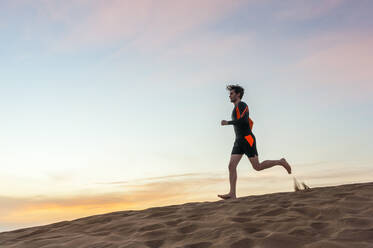 Man running at sunset in the dunes, Gran Canaria, Spain - DIGF12583