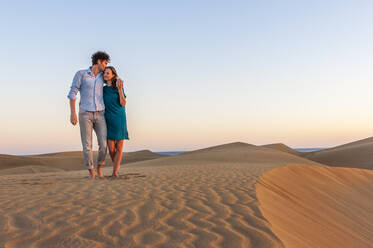 Affectionate couple walking in the dunes at sunset, Gran Canaria, Spain - DIGF12595