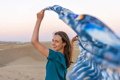 Portrait of happy woman holding cloth at sunset in the dunes, Gran Canaria, Spain - DIGF12598