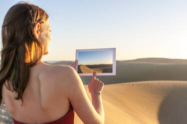 Woman taking a picture with tablet at sunset in the dunes, Gran Canaria, Spain - DIGF12601