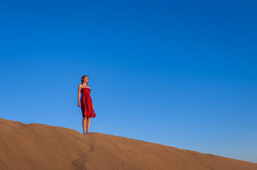 Woman in red dress standing in the dunes under blue sky, Gran Canaria, Spain - DIGF12604