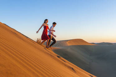 Couple running down dunes at sunset, Gran Canaria, Spain - DIGF12607