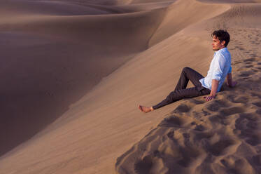 Man sitting at sunset in the dunes, Gran Canaria, Spain - DIGF12610