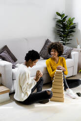 Two young woman sitting on the floor at home stacking boxes in the living room - GIOF08277