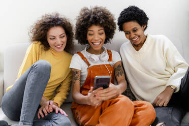 Group picture of three laughing friends sitting on couch taking selfie with smartphone - GIOF08304