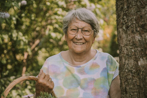 Happy retired senior woman holding basket while standing by tree at garden - MFF05865