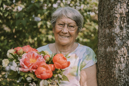Retired senior woman holding fresh peony bouquet by tree at garden - MFF05871