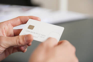 Hands of mid adult man holding blank white credit card - DIGF12670