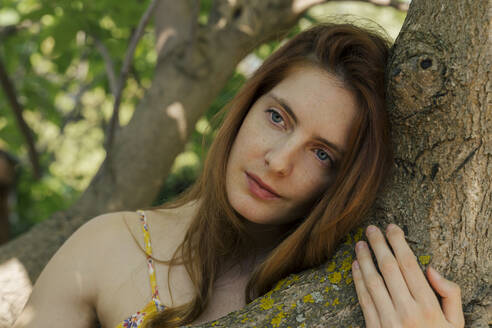 Thoughtful young woman looking away while leaning on tree trunk in garden - AFVF06429