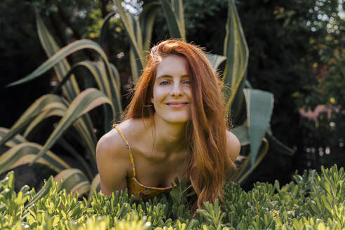 Smiling young beautiful woman leaning over plants at garden - AFVF06432