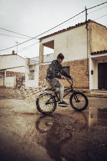 Teenage boy splashing water in puddle while riding bicycle on street during rainy season - ACPF00728