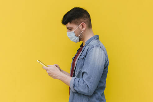 Man with protective mask looking at cell phone in front of yellow background - AGGF00071