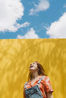 Cheerful young woman with mouth open standing over yellow wall against cloudy sky - AFVF06436