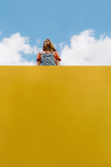 Young woman standing above yellow wall against cloudy sky - AFVF06439