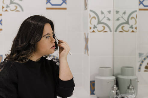 Young woman with down syndrome applying make-up in front of bathroom mirror at home - DCRF00211