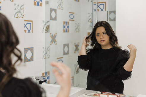 Beautiful young woman with down syndrome making hair in front of bathroom mirror at home - DCRF00214