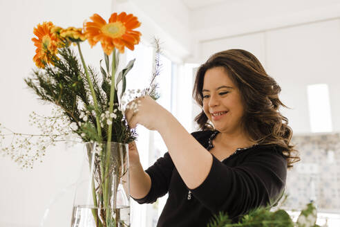 Happy young woman with down syndrome arranging flowers in vase at home - DCRF00226