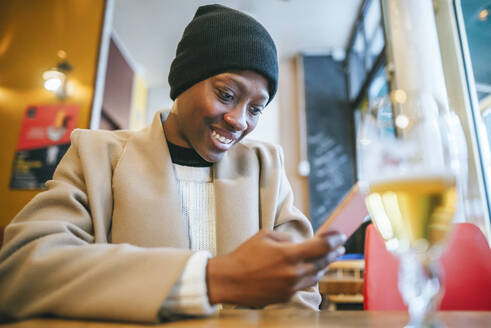 Happy young woman using smart phone in coffee shop - KIJF03044
