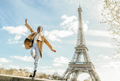 Excited woman jumping from retaining wall with Eiffel Tower in background, Paris, France - KIJF03053