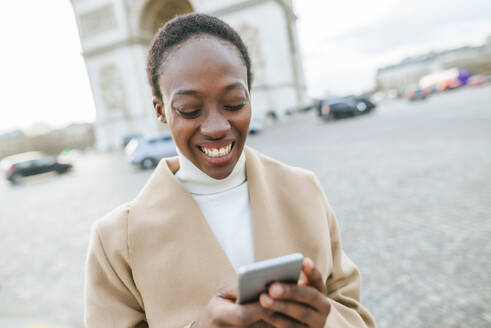 Happy young woman using smart phone against Arc de Triomphe during sunny day, Paris, France - KIJF03077