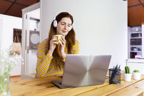 Young woman wearing headphones holding mug while using laptop on desk at home - AFVF06466