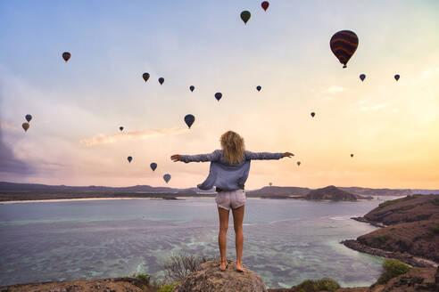 Indonesia, West Nusa Tenggara, Hot air balloons flying over lone woman standing on rocky shore with raised arms - KNTF04657