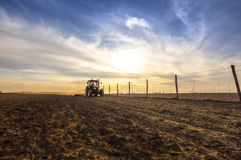 Farmer in tractor plowing agricultural land against cloudy sky - NOF00100