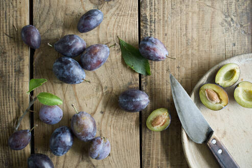 Kitchen knife and fresh plums on wooden surface - ASF06628