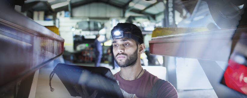 Focused male mechanic with headlight and diagnostic equipment working under car in auto repair shop - HOXF06458