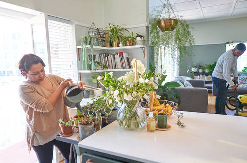 Mature woman watering houseplants in kitchen - CAIF28068