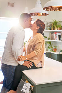 Affectionate mature couple kissing on kitchen island - CAIF28086