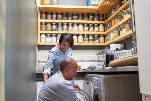 Happy couple doing laundry in kitchen - CAIF28107
