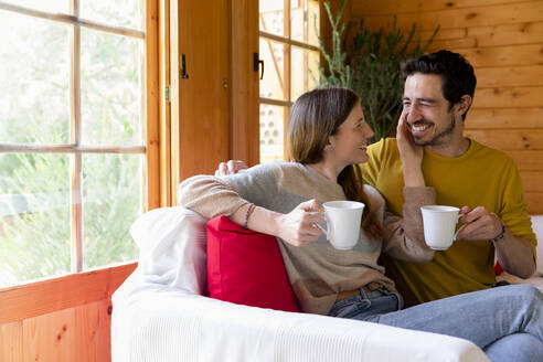 Romantic couple holding coffee mugs looking at each other while sitting on sofa in log cabin - LVVF00003