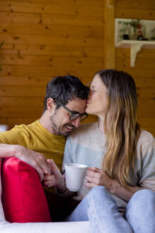 Loving woman kissing on man forehead while relaxing in log cabin - LVVF00009